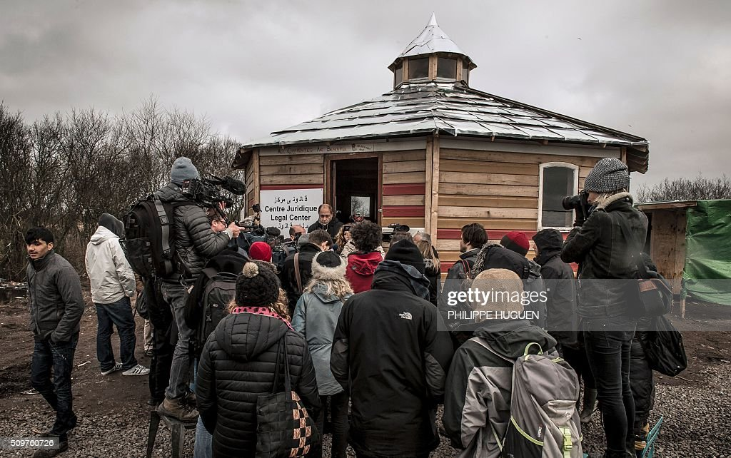 Marianne Humbersot (R) head of the Legal Centre and French lawyer Raymond Blet hold a press conference in the so-called 'Jungle' migrant camp in Calais, northern France, on February 12, 2016, to announce that dozens of complains will be filed for violence against migrants by police forces. / AFP / PHILIPPE HUGUEN