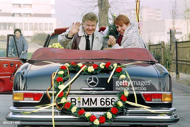 Marianne Kopper of East Berlin and her husband Wolfgang Spitz of West Berlin wave to photographers on November 20 1989 after their wedding ceremony...