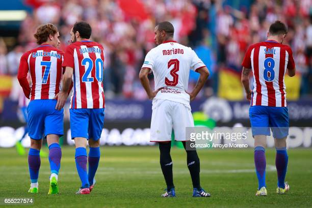 Mariano Ferreira of Sevilla FC reacts as Atletico de Madrid palyers Antoine Griezmann celebrates scoring their second goal with teammate Juan...
