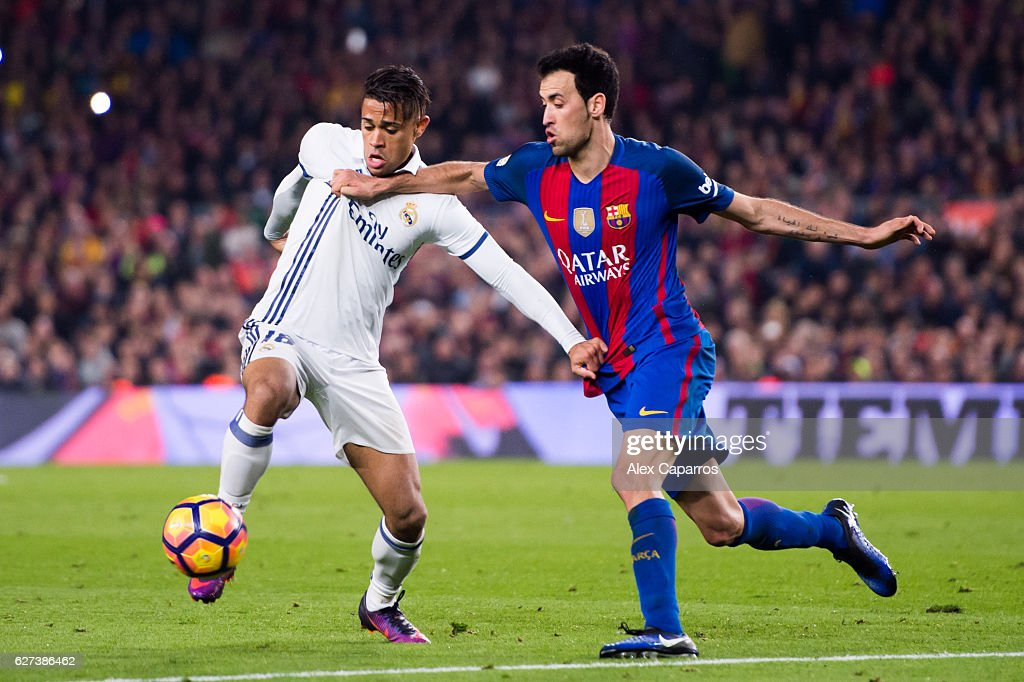 Mariano of Real Madrid CF and Sergio Busquets of FC Barcelona fight for the ball during the La Liga match between FC Barcelona and Real Madrid CF at...