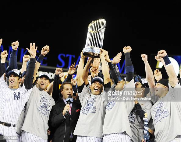 Mariano Rivera holds trophy as New York Yankees celebrate on the field after winning the 2009 World Series at Yankee Stadium They defeated the...