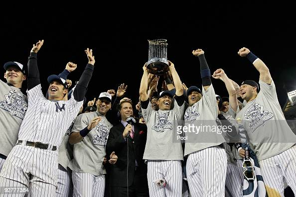 Mariano Rivera of the New York Yankees holds the trophy as he celebrates with Derek Jeter Jorge Posada and other teammates celebrates with the trophy...