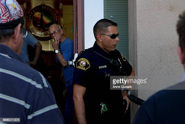 Maricopa volunteer Police Officer Andrew Zamacona talks with residents outside Gusher Hall before the start of the city council meeting in Maricopa...