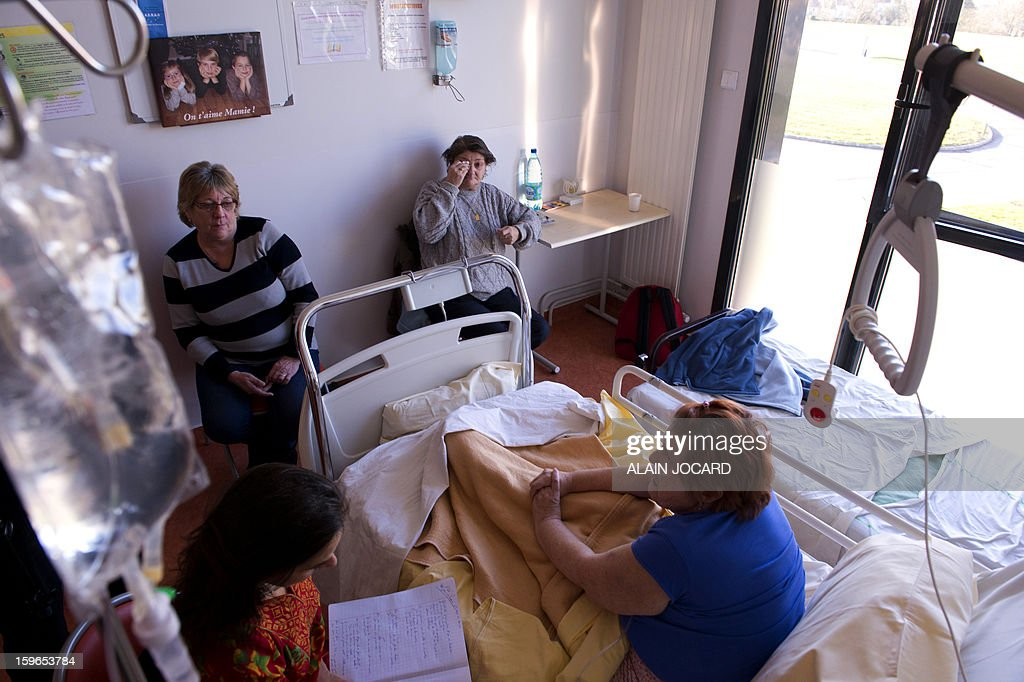 BONNET - Marie (R), a 60 years old woman affected by a cancer, hospitalized in a palliative care unit, is pictured in her room with relatives and her biograph, Valeria Milewski (L), on January 16, 2013, in Chartres. In this palliative unit sick people can tell their story to a biograph and leave a message for their loved ones.
