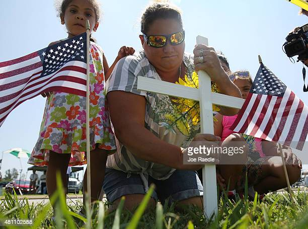 Marie Anderson places a cross in the ground as she pays her respects to those killed and injured while visiting a memorial placed in front of the...