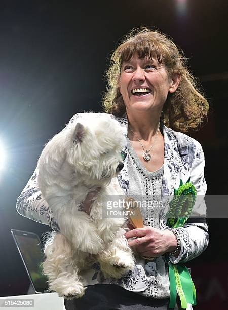Marie Burns smiles as she holds 'Burneze Geordie Girl' the West Highland White Terrier winner of the Best in Show competition at the Crufts Dog Show...
