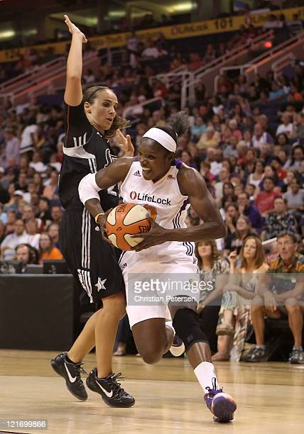 Marie FerdinandHarris of the Phoenix Mercury drives the ball past Becky Hammon of the San Antonio Silver Stars during the WNBA game at US Airways...