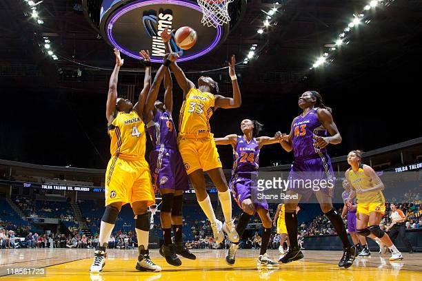 Marie FerdinandHarris of the Phoenix Mercury fights for a rebound with Amber Holt and Tiffany Jackson of the Tulsa Shock during the WNBA game on July...