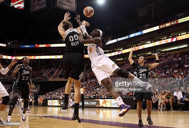 Marie FerdinandHarris of the Phoenix Mercury has her shot blocked by Ruth Riley of the San Antonio Silver Stars during the WNBA game at US Airways...