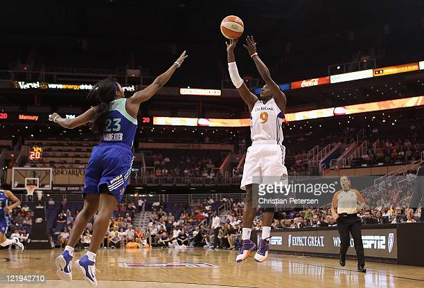 Marie FerdinandHarris of the Phoenix Mercury puts up a three point shot over Cappie Pondexter of the New York Liberty during the WNBA game at US...