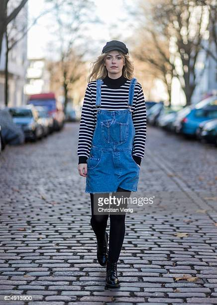 Marie Jaster wearing a black white striped Zara sweater a blue denim dungarees denim dress vintage a black lindex flat cap tights and Dr Martens...