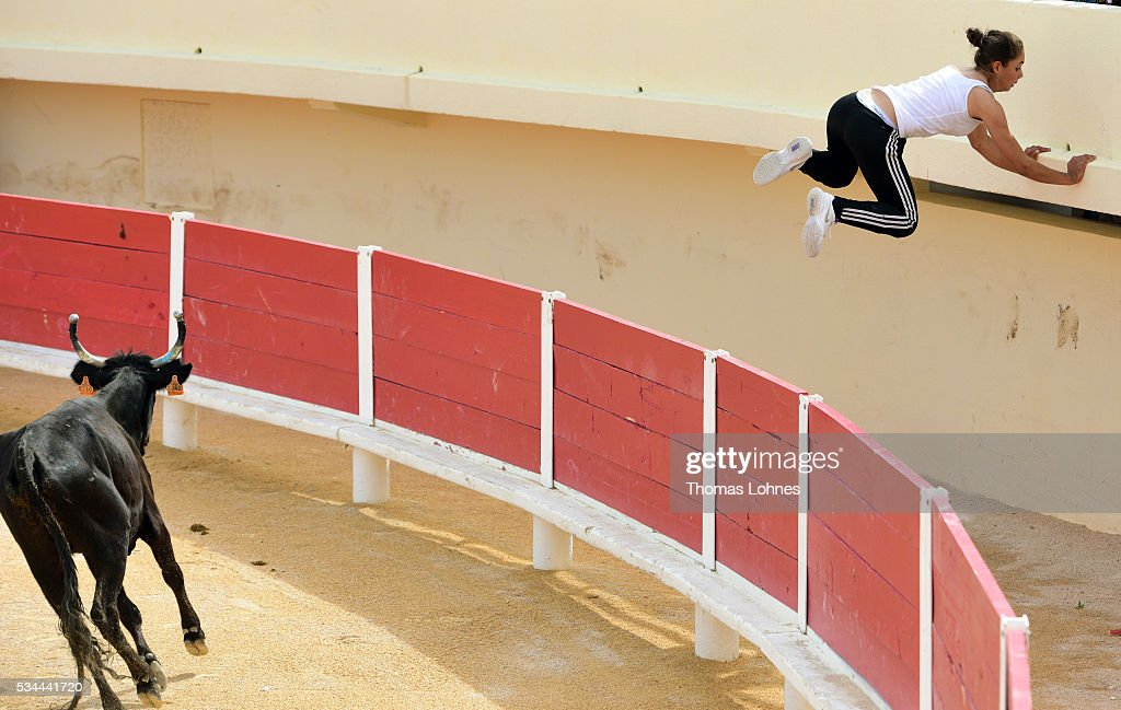 Marie Segretier (18) jumps out of the arena after trying to touch a bull between the eyes during a presentation of a special form of bullfighting in the Camargue on May 26, 2016 in Saintes-Maries-de-la-Mer near Arles, France. Traditional horsemen, so called Guardians, celebrate the day in memory of theMarquis de Baroncelli and show tourist how they work. Marie works with horses and is the only 'cow girl' in the area of Staintes-Maries-de-la-Mer (Camargue). She started with 5-6 years.