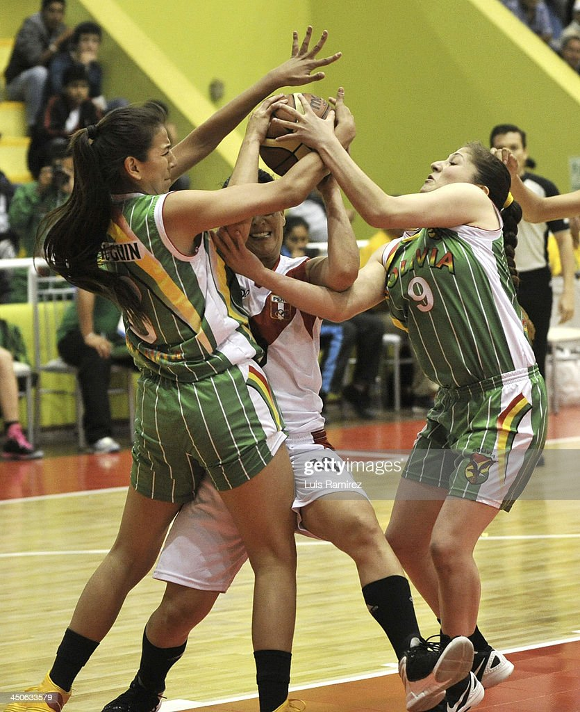 Mariel Quiroz of Peru struggles for the ball with Romina Rodriguez and Maria Olguin of Bolivia during a match between Peru and Bolivia in Women's Basketball Qualifiers as part of the XVII Bolivarian Games Trujillo 2013 at Coliseo Colegio Manuel Pardo on November 19, 2013 in Chiclayo, Peru.