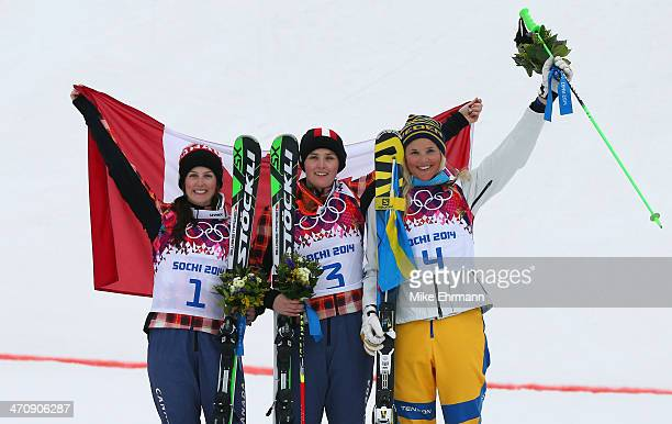 Marielle Thompson of Canada celebrates winning the gold medal with silver medalist Kelsey Serwa of Canada and bronze medalist Anna Holmlund of Sweden...