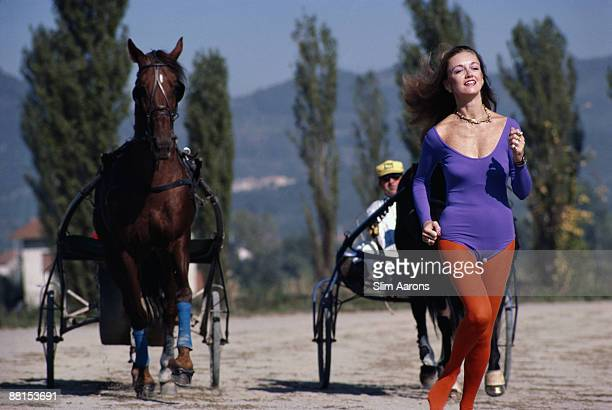 MarieLouise Scio in leotard and tights running between two racing sulkies in the health resort of Montecatini Italy November 1980