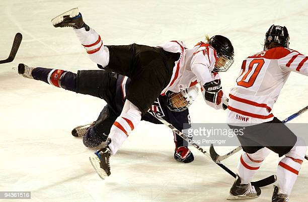 MariePhilip Poulin of Canada and Caitlin Cahow of the USA collide while pursuing the puck during their Women's Ice Hockey match at the Magness Arena...