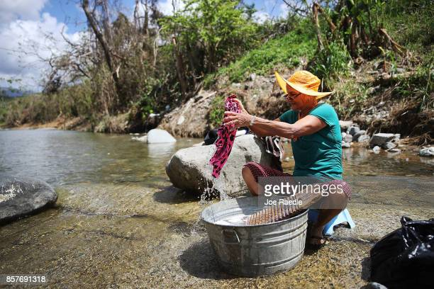 Marila Leon washes clothes in a river in the wake of the devastation left across the island by Hurricane Maria on October 4 2017 in Utuado Puerto...