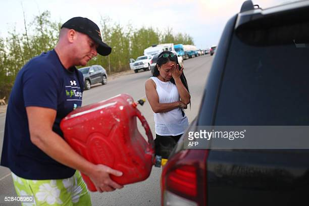 Marilou Wood fights back tears as husband Jim Wood fills up his car with gas after fleeing forest fires in Fort McMurray on May 4 2016 Numerous...