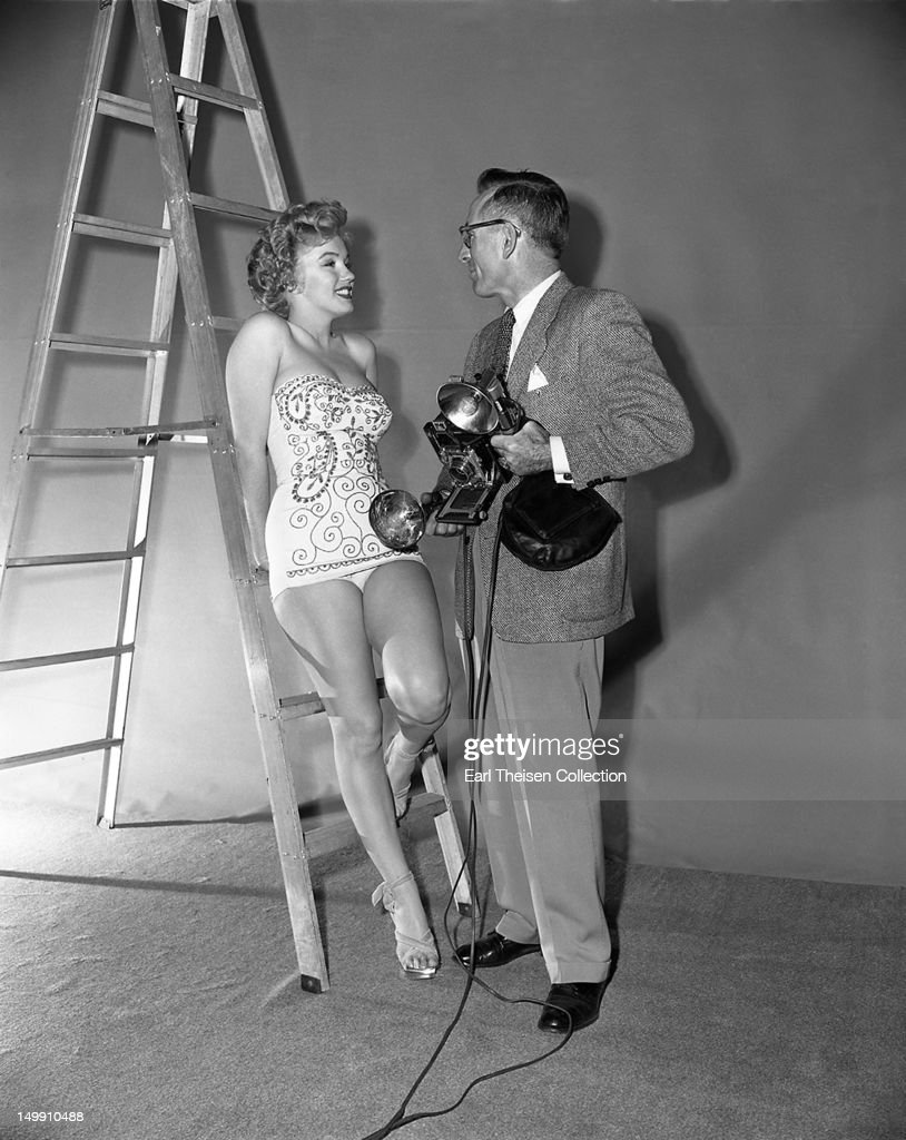 Marilyn Monroe chats with photographer Earl Theisen during a portrait session in February 1952 in Los Angeles, California.