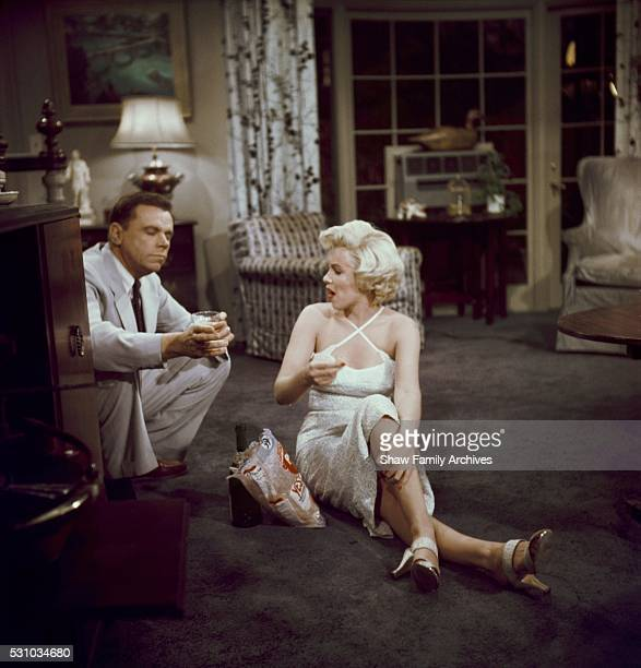 Marilyn Monroe eats potato chips and drinks a champagne sitting on the floor with costar Tom Ewell in 1954 during the filming of 'The Seven Year...