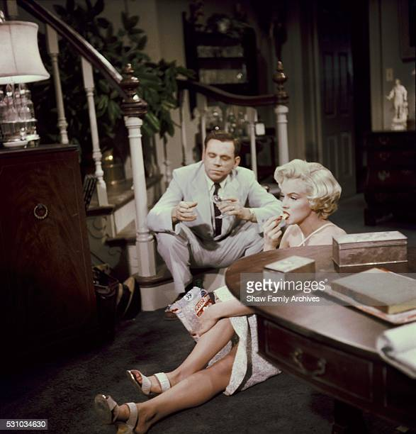Marilyn Monroe eats potato chips and drinks champagne sitting on the floor with costar Tom Ewell in 1954 during the filming of 'The Seven Year Itch'...