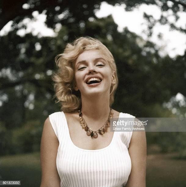 Marilyn Monroe laughs as she poses wearing an amber bead necklace in 1957 in Amagansett New York