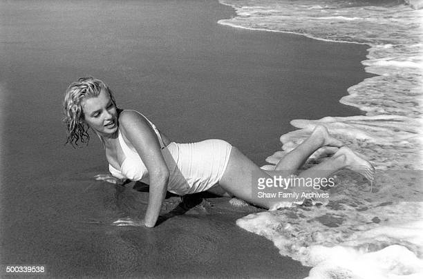 Marilyn Monroe lies on the beach at the edge of the water in 1957 in Amagansett New York