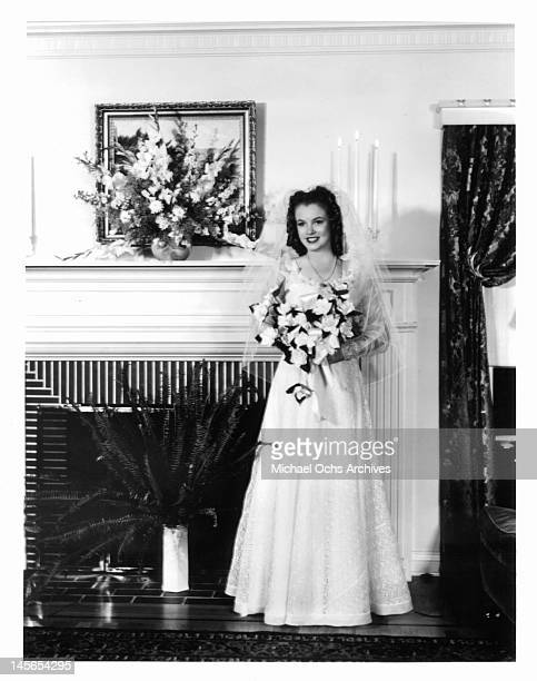 Marilyn Monroe on the day of her wedding day to James Dougherty in front of a fireplace in her wedding dress and holding a bouquet Los Angeles 1942