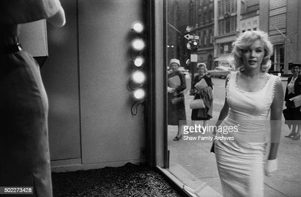 Marilyn Monroe seen through the window of a department store on Fifth Avenue with onlookers in the street in 1957 in New York New York