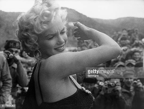 Marilyn Monroe shields her eyes from flashbulbs while entertaining US troops in South Korea