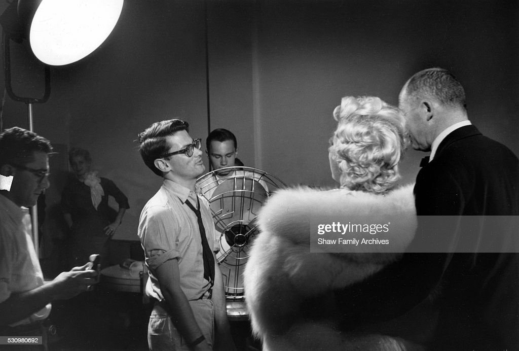 Marilyn Monroe stands wearing a white fur stole wrap with director Billy Wilder for a publicity shoot with Richard Avedon in his studio during the...