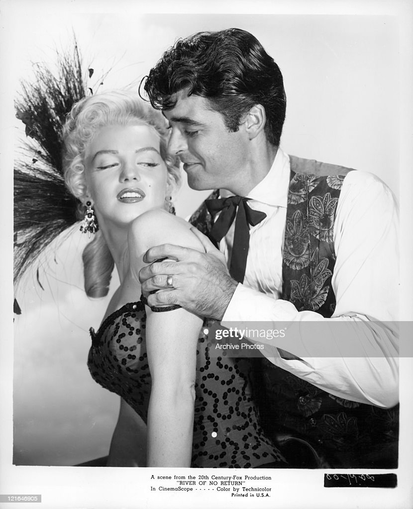 Marilyn Monroe turning as Rory Calhoun pulls her closer to him in a scene from the film 'River Of No Return' 1954