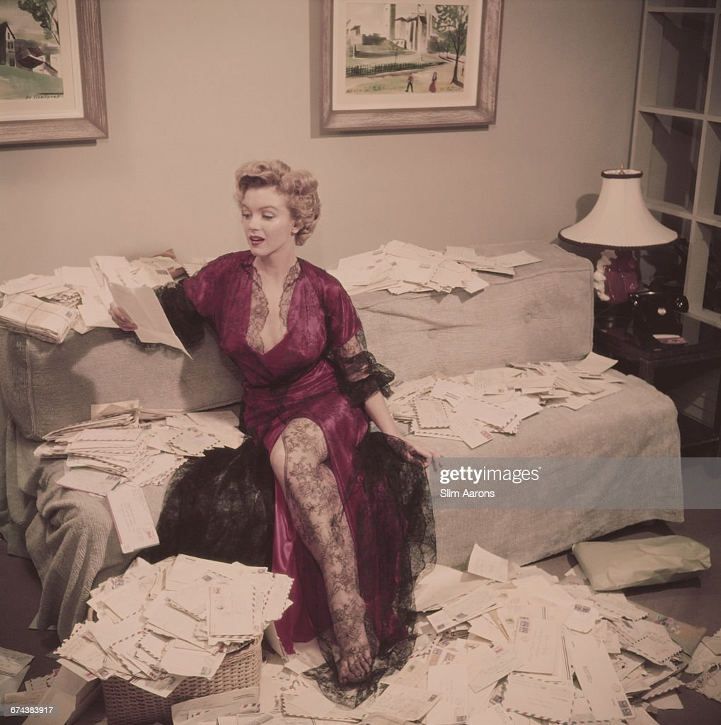 Marilyn Monroe wearing a red negligee trimmed with black lace sorts out her fan mail shortly after her film 'The Asphalt Jungle' had been released...
