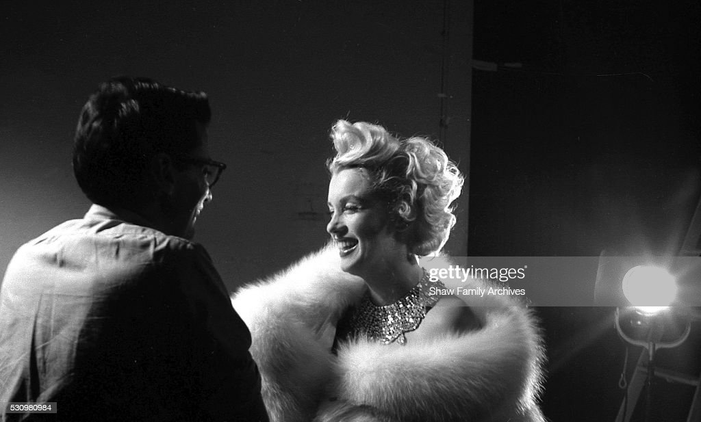 Marilyn Monroe wearing a white fur stole wrap with photographer Richard Avedon as they prepare for a publicity photo shoot in his studio during the...