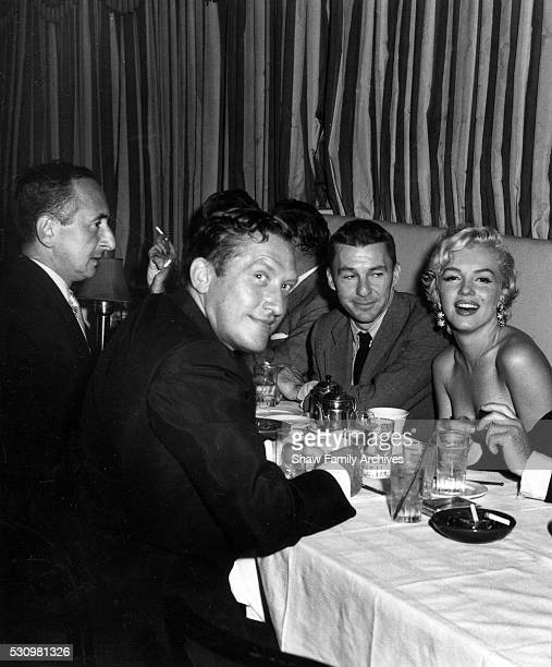 Marilyn Monroe with producer Darryl Zanuck actor David Wayne playwright Sidney Kingsley and newspaper columnist Leonard Lyons at the wrap party for...