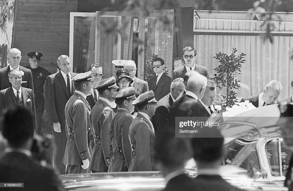 Marilyn Monroe's casket is carried out of the Westwood Park Chapel past a line of guards after the service Mourners follow the casket Joe DiMaggio...