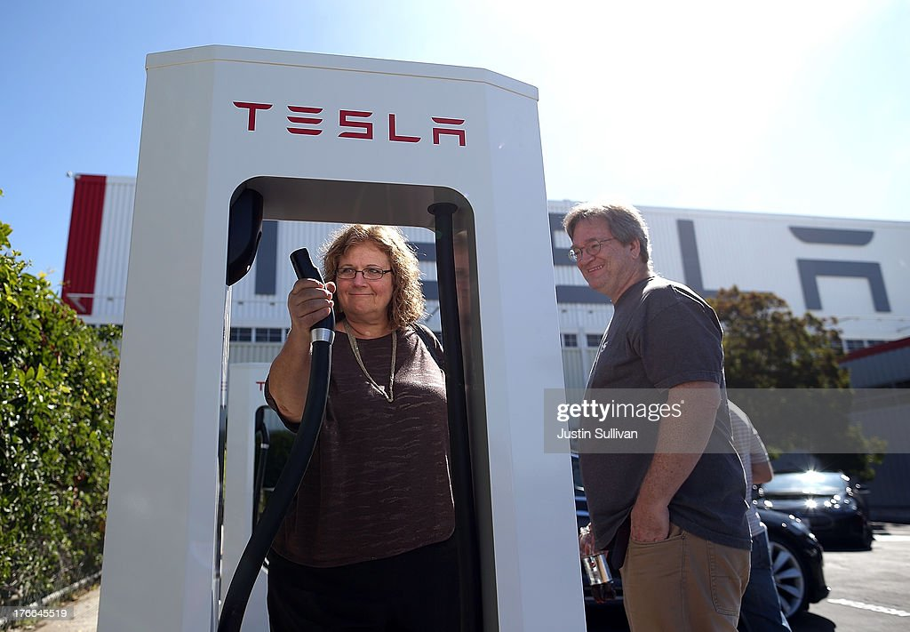 Marilyn Tearse (L) and Ken Doyle (R) inspect a new Tesla Supercharger outside of the Tesla Factory on August 16, 2013 in Fremont, California. Tesla Motors opened a new Supercharger station with four stalls for public use at their factory in Fremont, California. The Superchargers allow owners of the Tesla Model S to charge their vehicles in 20 to 30 minutes for free. There are now 18 charging stations in the U.S. with plans to open more in the near future.
