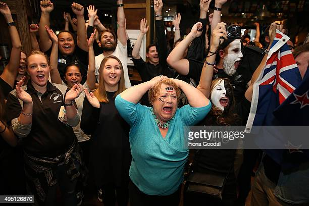 Marilynna Burton celebrates with rugby fans at The Fox Sports Bar in Auckland watch the 2015 Rugby World Cup Final match between the New Zealand All...