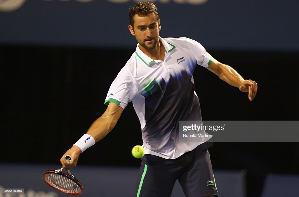 Marin Cilic of Croatia returns a shot to Roger Federer of Switzerland during Rogers Cup at Rexall Centre at York University on August 7, 2014 in Toronto, Canada.