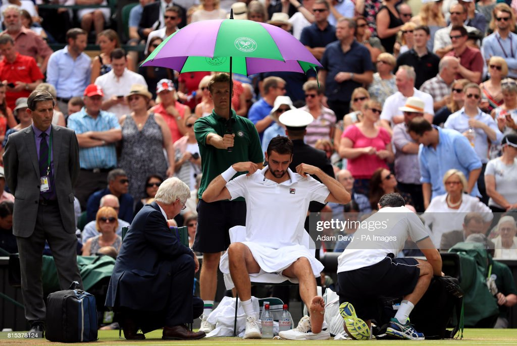 Marin Cilic receives treatment during a medical time out in his match against Roger Federer in the Gentlemen's Singles Final on day thirteen of the Wimbledon Championships at The All England Lawn Tennis and Croquet Club, Wimbledon.