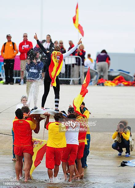 Marina Alabau Neira of Spain is carried onshore by team mates as she celebrates winning the gold medal in the RSX Women's Sailing on Day 11 of the...