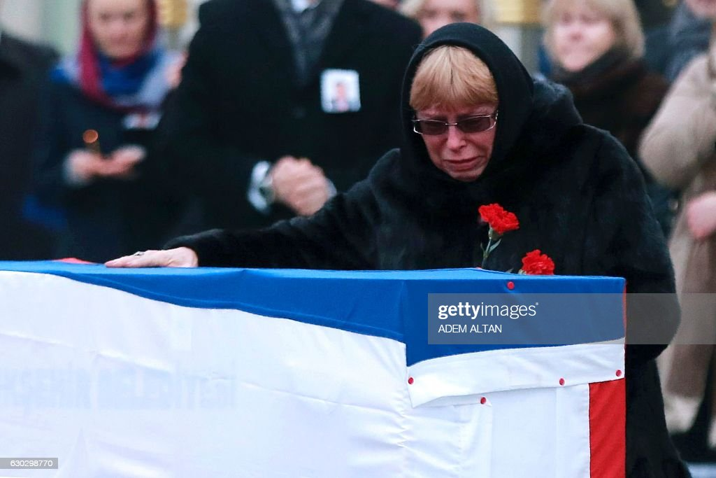 TOPSHOT - Marina Davydova Karlova, widow of late Russian Ambassador to Turkey Andrei Karlov, reacts in front of his coffin, during a ceremonial farewell with full state honours on the tarmac of Ankara's Esenboga Airport on December 20, 2016, before the coffin is transported on a Russian plane for Moscow. Veteran diplomat Andrei Karlov was shot nine times in the back by an off-duty Turkish policeman at the opening of an exhibition of Russian photography on December 19, 2016. The brazen killing stunned Ankara and Moscow, which have rowed repeatedly over the Syria conflict but in recent weeks have begun cooperating closely on the evacuations from war-wrecked Aleppo. ALTAN