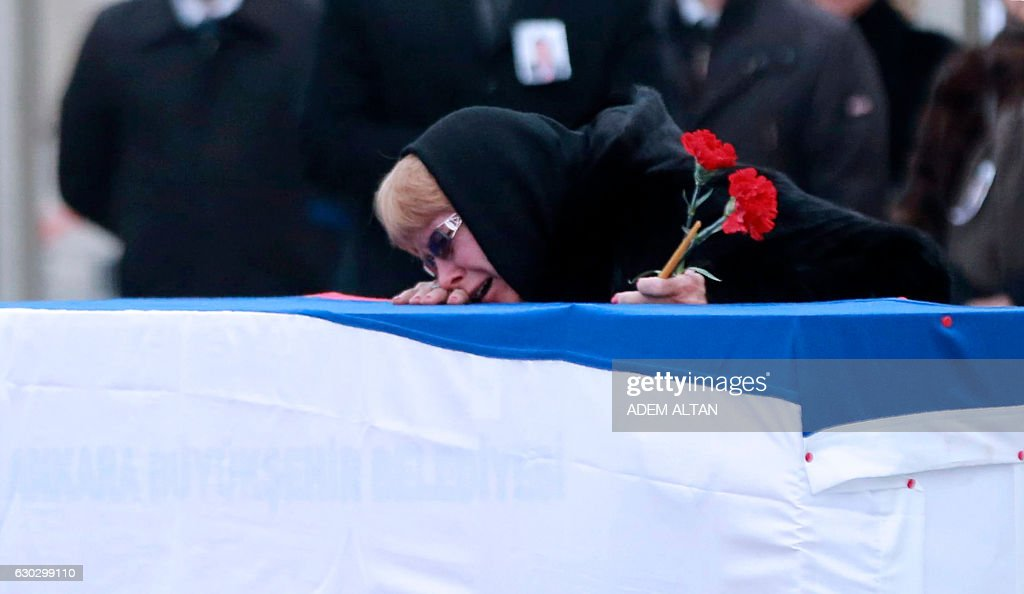 Marina Davydova Karlova, widow of late Russian Ambassador to Turkey Andrei Karlov, reacts in front of his coffin, during a ceremonial farewell with full state honours on the tarmac of Ankara's Esenboga Airport on December 20, 2016, before the coffin is transported on a Russian plane for Moscow. Veteran diplomat Andrei Karlov was shot nine times in the back by an off-duty Turkish policeman at the opening of an exhibition of Russian photography on December 19, 2016. The brazen killing stunned Ankara and Moscow, which have rowed repeatedly over the Syria conflict but in recent weeks have begun cooperating closely on the evacuations from war-wrecked Aleppo. ALTAN