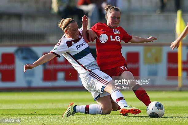 Marina Hegering of Leverkusen is challenged by Melanie Behringer of Muenchen during the Allianz FrauenBundesliga match between Bayer 04 Leverkusen...