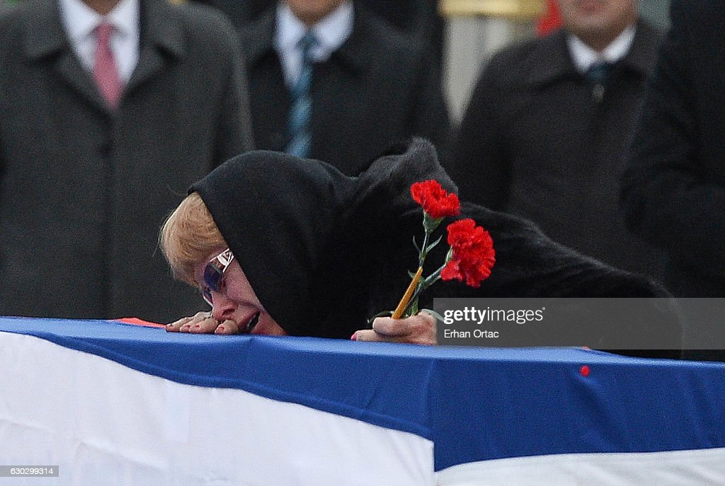 Marina Karlov mourns her husband laying her head on top a flag-wrapped coffin of late Russian Ambassador to Turkey Andrei Karlov before being carried to a plane by Turkish soldiers during a ceremony at Esenboga airport on December 20, 2016 in Ankara. Turkey. Russia's ambassador to Turkey, Andrey Karlov, was shot dead by a Turkish policeman shouting 'Don't forget Aleppo! Don't forget Syria' at an art exhibition in the Turkish capital of Ankara yesterday.