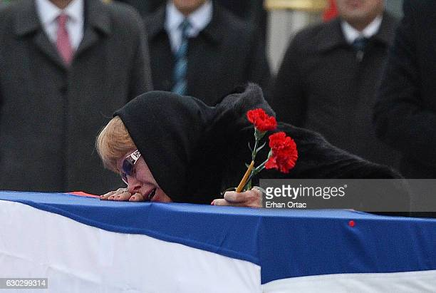 Marina Karlov mourns her husband laying her head on top a flagwrapped coffin of late Russian Ambassador to Turkey Andrei Karlov before being carried...