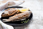 Marinated fried fish carp. Spicy fish fry with spices and lemon on plate, selective focus