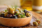Close-up shot of marinated olives with herbs and spices on rustic table.