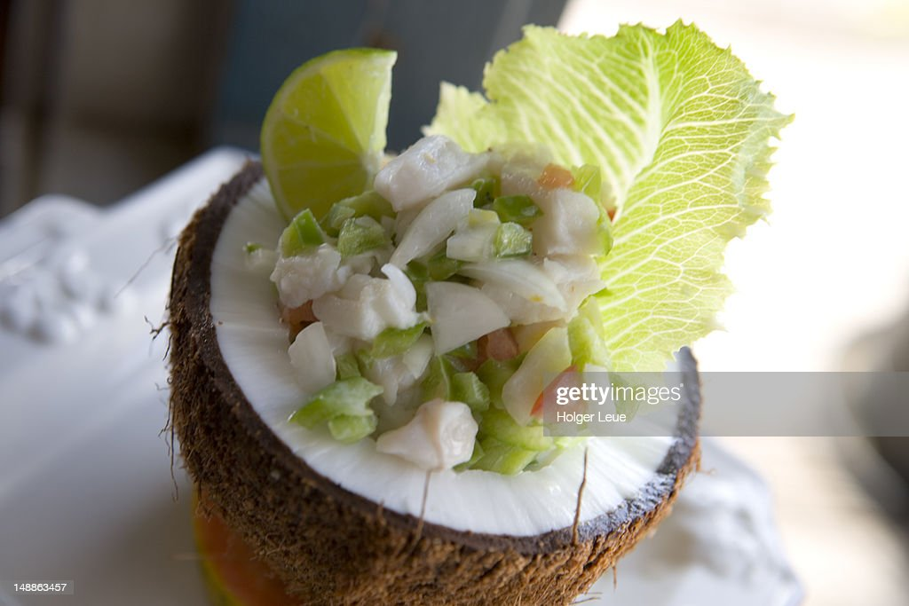 Marinated raw fish salad served in coconut at Surf & Turf Restaurant. : Stock Photo