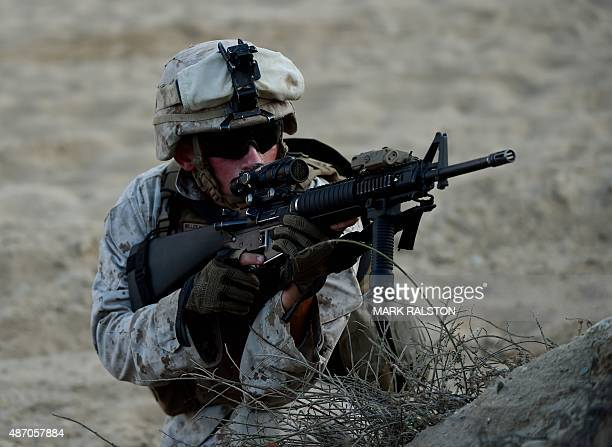 Marine aims his weapon during an amphibious landing operation with the Japan Maritime SelfDefense Force at the Dawn Blitz 2015 exercise in Camp...